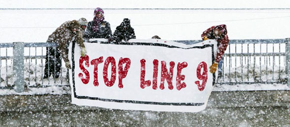 Local activists participate in a protest against the Line 9 pipeline, hanging their banner over the Dundas Street bridge. The Line 9 pipeline crosses over 29 rivers, and three major roads in Belleville.